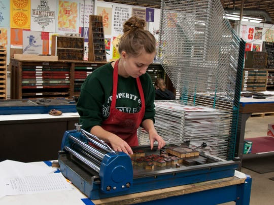 A workshop participant sets up the press at Hamilton Wood Type & Printing Museum in Two Rivers.