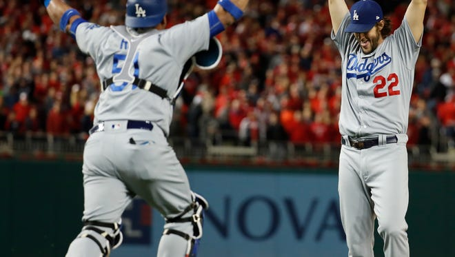 Los Angeles Dodgers pitcher Clayton Kershaw and catcher Carlos Ruiz celebrate after Washington Nationals' Wilmer Difo struck out to end Game 5 of the National League Division Series at Nationals Park. The Dodgers won 4-3.
