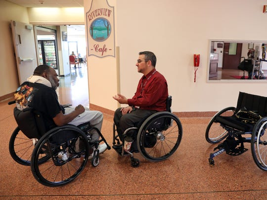 Matt Castelluccio, center, of White Plains chats with Jerome Kleckley of New City at Helen Hayes Hospital, where Castelluccio received his rehab and now works, July 12, 2018 in Stony Point. Castelluccio, 41, became paralyzed in a motorcycle accident in 2003. Despite no leg function and very little arm function, he plays adaptive rugby, where he met Kleckley, and softball.