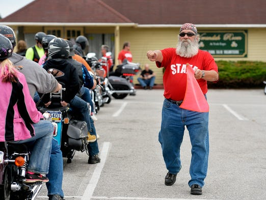 Bill Strickler of Dover Township directs arriving motorcyclists