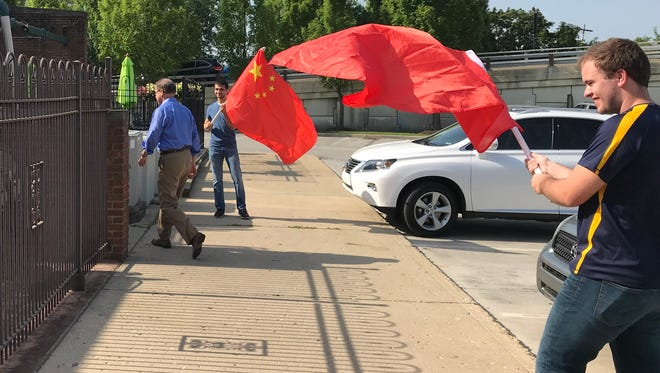 Members of the Indiana Democratic Party wave Chinese flags to greet Mike Braun, Republican candidate for U.S. Senate as he arrived for a campaign stop at Preston's in downtown Lafayette. The protest with the flags was taunting reference to Braun's auto parts distribution company importing goods from China.