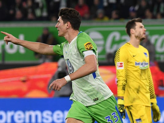 Wolfsburg's Mario Gomez, left, celebrates scoring against Berlin next to Hertha's goalkeeper Rune Jarstein during the German Bundesliga soccer match between VfL Wolfsburg and Hertha BSC at the Volkswagen Arena in Wolfsburg, Germany, Sunday Nov. 5, 2017. (Peter Steffen/dpa via AP)