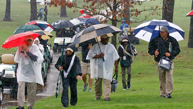 Standard bearers, caddies, officials, fans and golfers rush off the Country Club of Jackson golf course as a weather warning horn sounds during the resumption of Friday's second round of the Sanderson Farms Classic golf tournament, Saturday, Nov. 7, 2015, in Jackson, Miss.(AP Photo/Rogelio V. Solis)