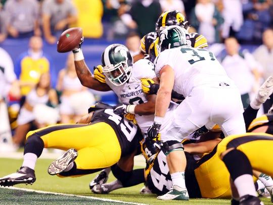 Michigan State running back L.J. Scott reaches across