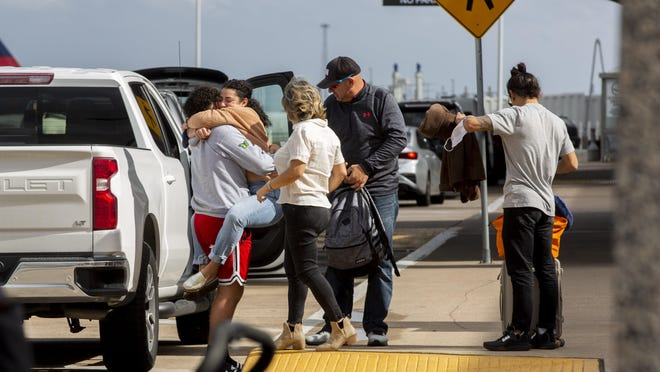 Abigail Santiago, 27, hugs her brother Angel, 16, outside the departure gates at Austin-Bergstrom International Airport on Tuesday. Austin Public Health officials are encouraging people to stay home for Thanksgiving to limit exposure to COVID-19.