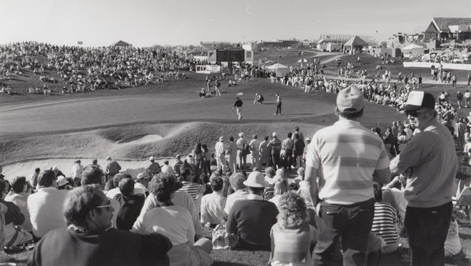 Onlookers watch as golfers make their puts at the Phoenix Open, Jan. 27, 1991.