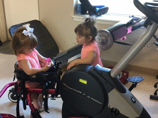 Allie Mae Carpenter opens an Easter egg as her sister, Audrey, looks on. Allie goes on an 'egg hunt' at therapy to practice gait training. With the support of a walker, she is able to bear weight on her legs and stand to retrieve the plastic eggs from their hiding places.
