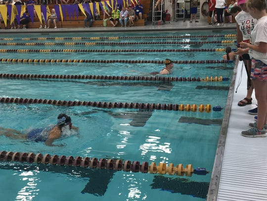 Swimmers take part in the 25-meter breaststroke at