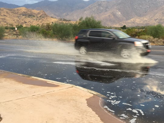 An SUV passes through a flooded area on Gene Autry Trail in Palm Springs. The city got hit by rain Monday morning and scattered showers are possible throughout the day.
