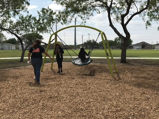 Students play on the renovated children's park before the ceremonial ribbon cutting at West Haven Park on Monday, Sept. 25, 2017.