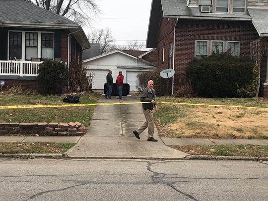 """Capt. Andy Chandler adjusts crime scene tape as Police Chief Billy Bolin talks with another officer at 906 Bellemeade Ave., where police found """"suspicious remains"""" in trash bags at the residence of Earl Martin. Martin was jailed this week on suspicion of murder and armed robbery."""