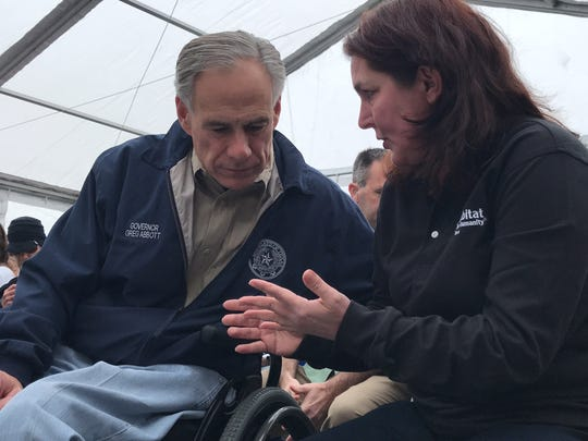 Texas Gov. Greg Abbott listens to Amy Parham, a representative for Habitat for Humanity of Aransas County, on how the organization has teamed up with Citgo to rebuild the Rockport community.