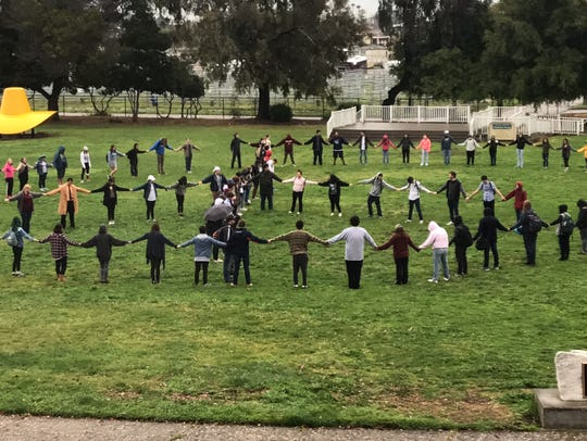 Students at Millennium Charter High School form a peace