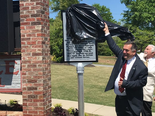 Six Mile Town Councilman James Atkinson and Ken Nabors of the Pickens County Historical Society unveil a historical marker in front of Town Hall.