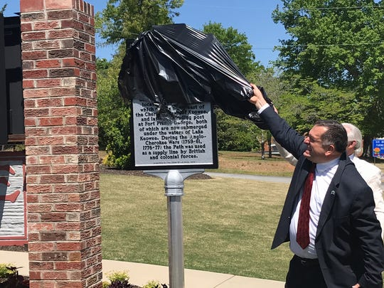Six Mile Town Councilman James Atkinson and Ken Nabors of the Pickens County Historical Society attempt to unveil a historical marker in front of Town Hall.