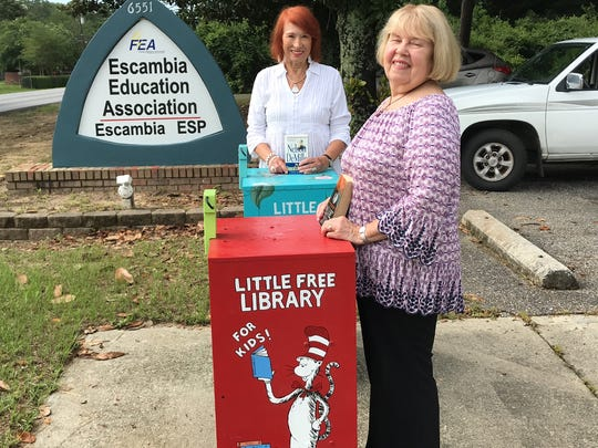 Retired teachers Annette Massicotte, center behind the aqua blue rack, and Barbara Beck, show off the Little Free Libraries at the Escambia Education Association on Palafox.