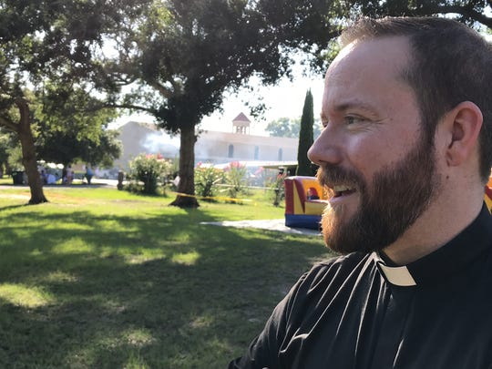 Father Nick Schumm, the priest at St. Thomas More Catholic Church, walks the parish grounds during MoreFest on Saturday.