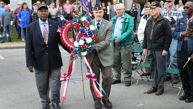 Y.T. Vaughan, left, and Joe Restivo, both veterans of the Korean and Vietnam wars, carry a wreath to the War Memorial Monument during the 2014 Veterans Day Celebration on the Public Square in Murfreesboro.