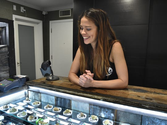 "Tian Scherer, a ""budtender"" at Buds & Roses in Studio City, California, talks with a client from behind the counter of the dispensery."