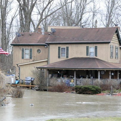 The Belle River floods the yard of a home on Indian