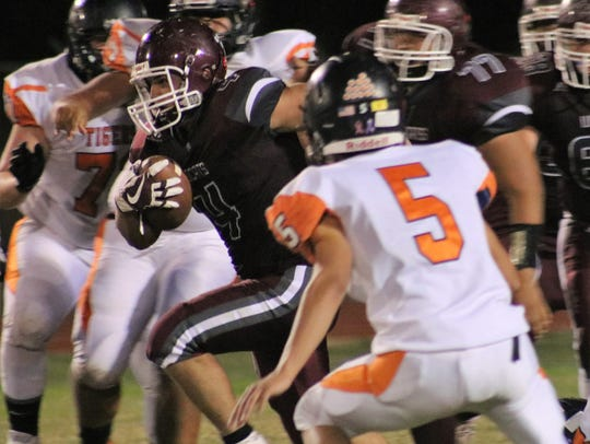 Tularosa's Toby Carrillo tries to find a hole to run