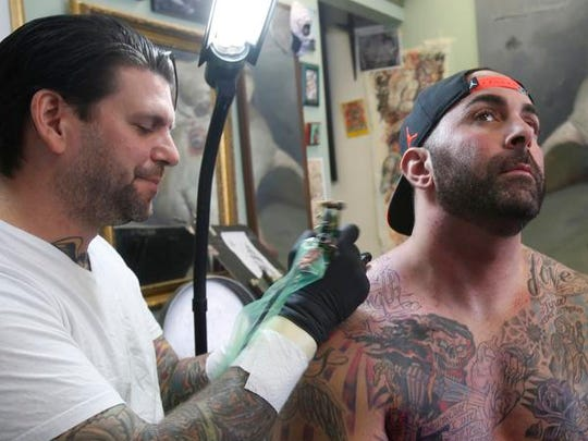 J.R. Maloney, owner of Vanguard Tattoo of Nyack, works on a memorial sleeve for Michael Sayegh of Thiells on Oct. 30, 2014.  The sleeve is principally in honor or Sayegh's sister who died of cancer as well as other family members.