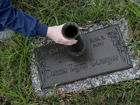 Amber Sawyer adjust the vase on the grave of her sister, Donna Sawyer, on March 16, 2018 in Pascagoula, Miss. Donna Sawyer committed in suicide in 1988 after the Jehovah's Witness community that she grew up in shunned her.