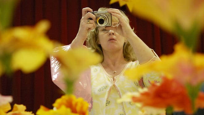 Rhonda Cope of North Port takes in a previous show  presented by the James E. Hendry Chapter of the American Hibiscus Society .
