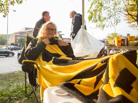 Susan Siedschlaw of Bettendorf keeps warm in the early