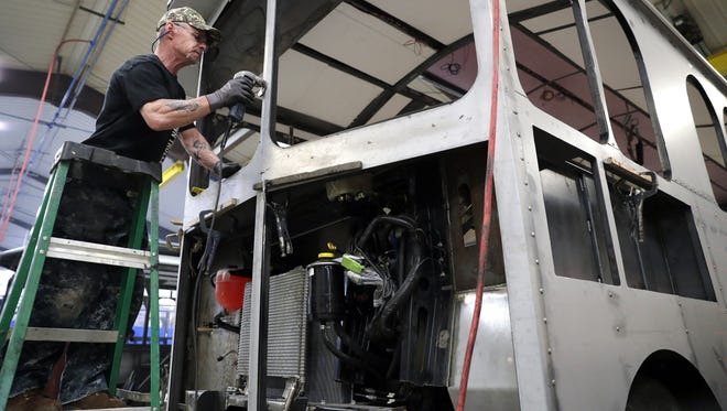 Ralph Blair, a fabricator in the sheeting department at Hometown Trolley in Crandon, Wis., works  on a Villager trolley that will go  to Juneau, Alaska once completed.