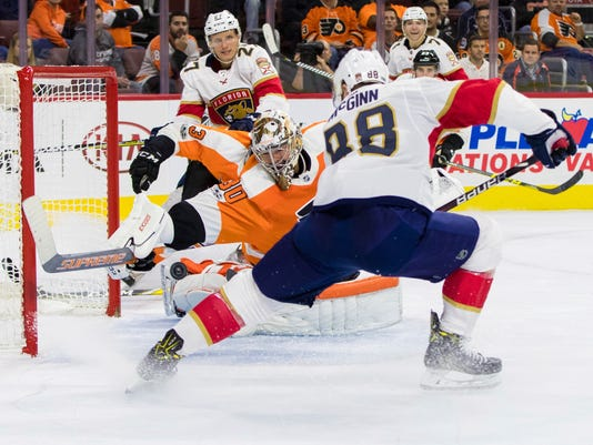 Philadelphia Flyers' Michal Neuvirth, of the Czech Republic, left, unable to stop the power play shot by Florida Panthers' Jamie McGinn, right, for a goal during the third period of an NHL hockey game, Tuesday, Oct. 17, 2017, in Philadelphia. The Flyers won 5-1. (AP Photo/Chris Szagola)