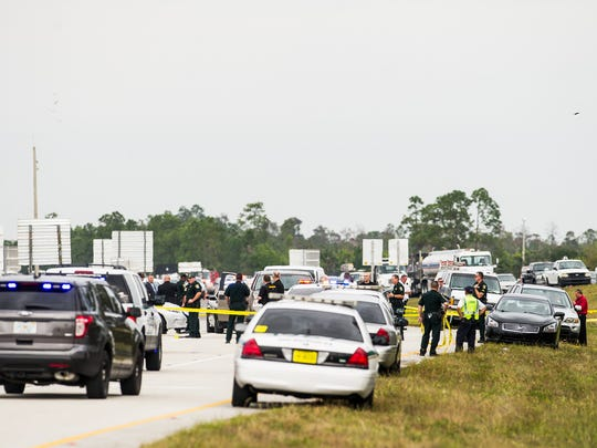 Law enforcement officers and emergency crews line the Interstate 75 off ramp at Corkscrew Road in Estero, Fla., on Monday, Nov. 14, 2016, after an officer-involved shooting.