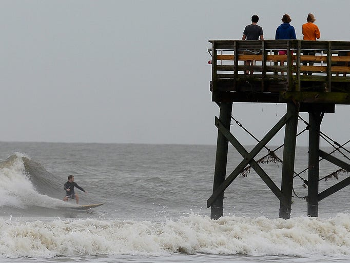 Boys, right, watch a surfer ride a wave near a pier