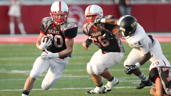 Center Grove running back Titus McCoy finds a big hole in the Warren Central defense during the season opener held at Center Grove High School on Friday, August 22, 2014.