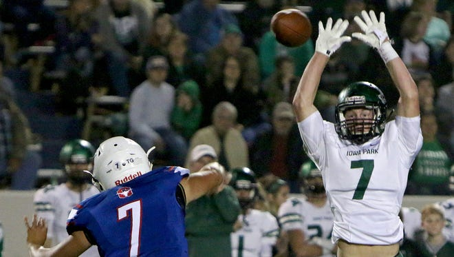 Iowa Park's Billy Pearson (right) leaps up to block a pass attempt by Graham quarterback Tucker Horn Friday night in Graham.