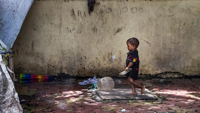 A young child walks along a sidewalk near a makeshift hut in Mumbai, India, on June 29, 2017.