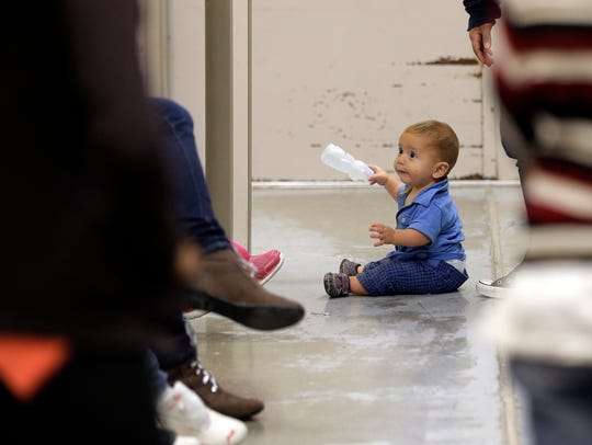 A toddler sits with other detainees at a Customs and