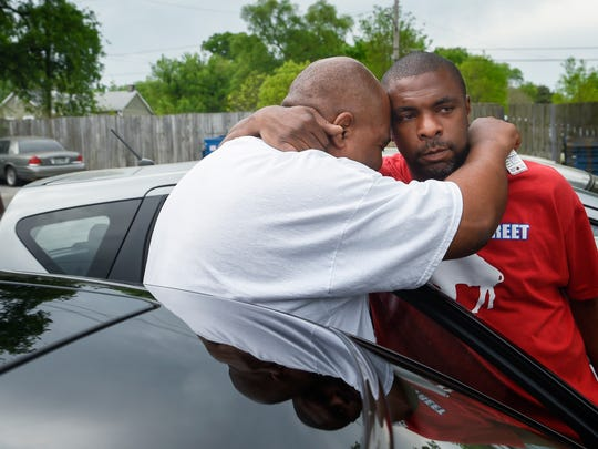 Bishop Marcus Campbell hugs old friend Ortago Thomas outside Wares Barbershop on Jefferson Street as another friend, Keith Vaughn, looks on.