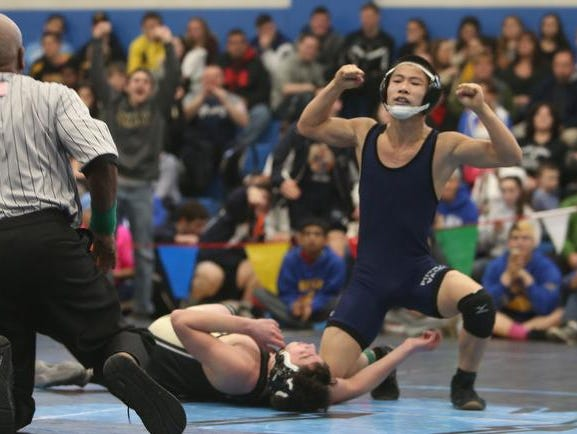 From right, Putnam Valley's Satoshi Abe celebrates after pinning Nanuet's Karl Burnich in the 113 pound weight class during the Division 2 sectional wrestling championship at Westlake High School in Thornwood Feb. 14, 2015.