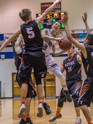 Piedra Vista's Brady Brown looks to shoot while being defended by Aztec's Tanner Brooks (5) and a host of other Tigers on Thursday at Jerry A. Conner Fieldhouse in Farmington.
