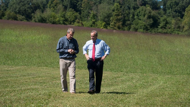 Todd Napier, left, president and CEO of The Development Corporation of Knox County, talks with Knox County Commissioner Bob Thomas in a field off of Worthington Lane in East Knox County on Sept. 15, 2015.