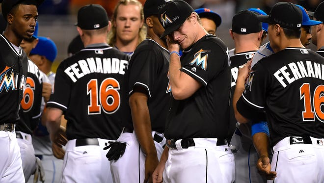 Marlins pitcher Tom Koehler wipes tears away after greeting all the New York Mets players at the pitchers mound in honor of the late Jose Fernandez.