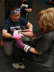 Katherine Reyes-Brooks, left, a certified Rock Steady Boxing trainer, helps a woman put on her gloves for a class.