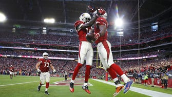 Arizona Cardinals wide receiver J.J. Nelson (14) greets running back David Johnson (31) following his touchdown against the Washington Redskins  in the 4th quarter of their  NFL game Sunday, Dec. 4, 2016 in Glendale, Ariz.