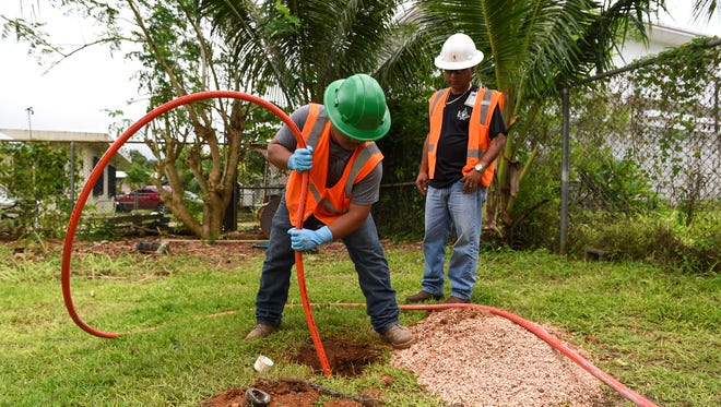 Guam Waterworks Authority trades helper Dominick San Nicolas, left, and acting supervisor Frank Sablan work to clear a sewage blockage at the Macheche Community Center in Dededo on Aug. 7, 2018.