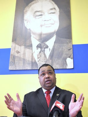 State Sen. Coleman Young II announces his candidacy for mayor of Detroit, sitting below a five-foot tall poster of his father, former Detroit Mayor Coleman A. Young.