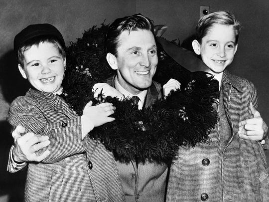 Kirk Douglas is greeted by his sons, Joel, left, 6, and Michael, 9, after arrival from Europe at Idlewild airport, Queens, New York City, USA on Dec. 15, 1953. Douglas, returning from 14 months of overseas filmmaking plans to spend Christmas with his sons who live with their mother Diana Dill, who is divorced from Douglas. CREDIT: AP ORG XMIT: APHSL48838 [Via MerlinFTP Drop]