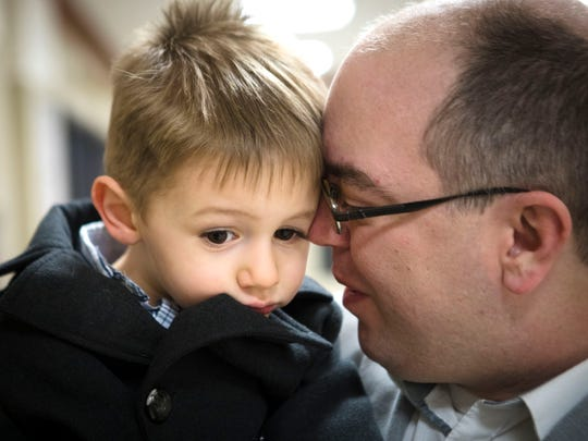 Thu., Jan. 25, 2018: Cameron Knight, city hall reporter at The Enquirer, holds Lucas, 2, before adoption proceedings began at Hamilton County Judge Ralph Winkler's courtroom. The Enquirer/Carrie Cochran
