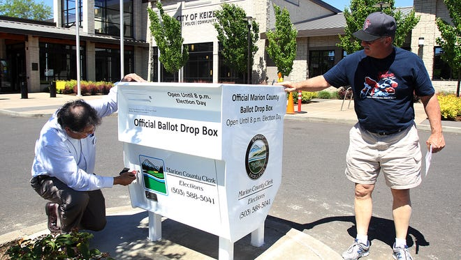 Statesman Journal file  Bill Burgess, Marion County Clerk, left, and Mark Caillier, former Keizer City Councilor, open up the first 24-hour ballot drop box in Marion County at Keizer Civic Center Sunday May 5, 2013.
