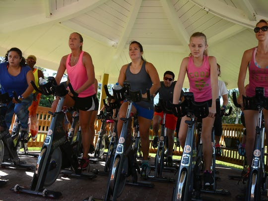Allison Morell, center, joins in a spin class under